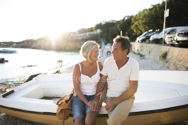 Старший пара, сидячи на краю човна на пляжі в вечірні сутінки — стокове фото