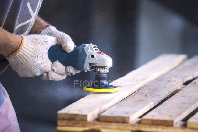 Nahaufnahme männlicher Hände, die Holz mit einem zufälligen Orbitalschleifer schleifen — Stockfoto