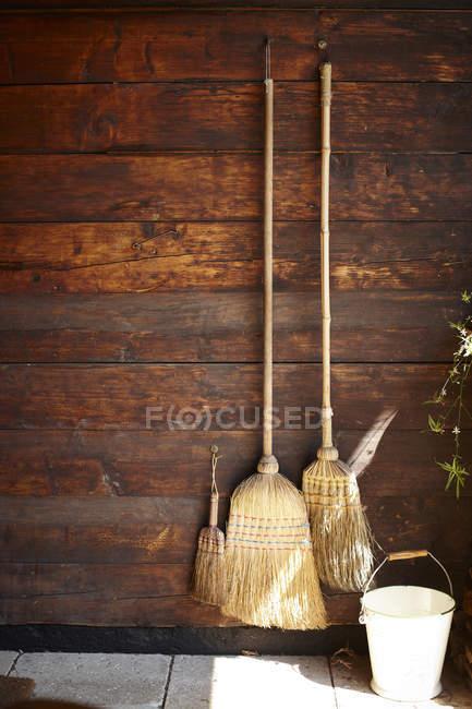 Drei Besen hängen an Holzwand — Stockfoto