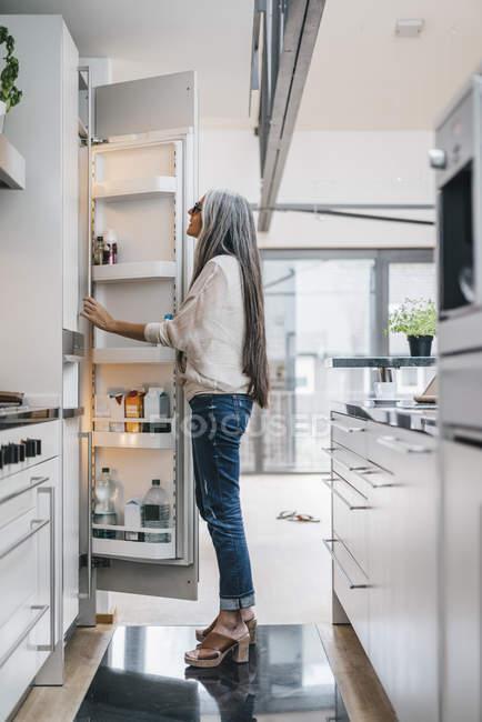 Woman looking in fridge in modern kitchen — Stock Photo