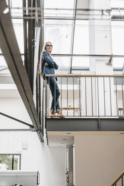 Confident businesswoman with long grey hair standing in a loft — Stock Photo