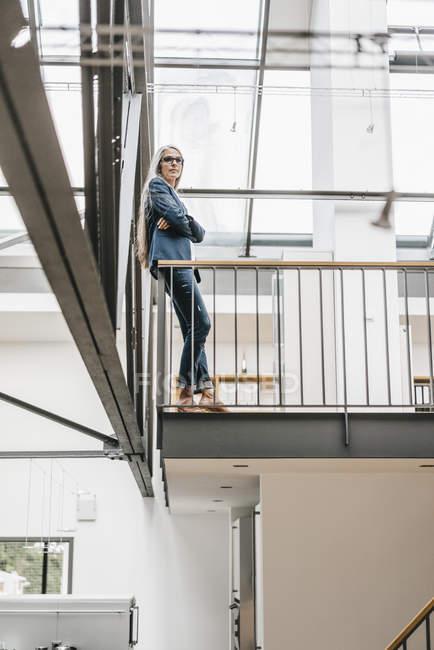 Donna di affari sicura con la condizione di capelli lunghi grigi in un loft — Foto stock