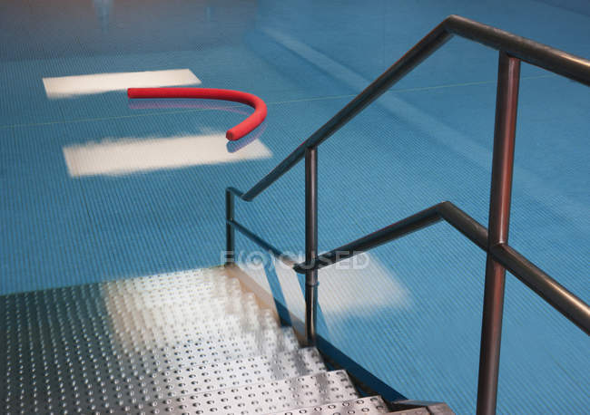 Access to indoor swimming pool with aqua noodle — Stock Photo