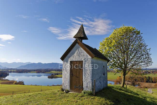 Capela de Mesnerhaus Alemanha, Baviera, na Aidlinger Hoehe com lago Riegsee — Fotografia de Stock
