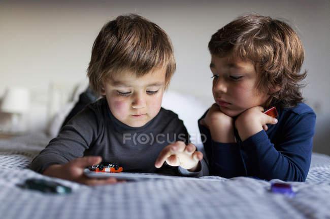 Dos chicos en la cama jugando con tableta digital - foto de stock