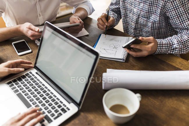Cropped image of colleagues at desk with smartphone, laptop and notepad — Stock Photo