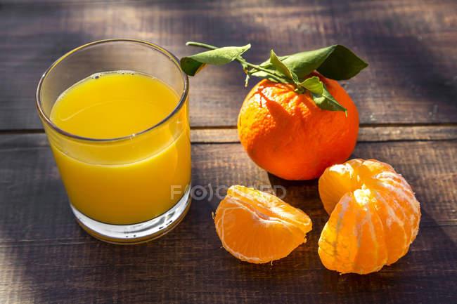 Tangarinas, suco em vidro na superfície de madeira — Fotografia de Stock