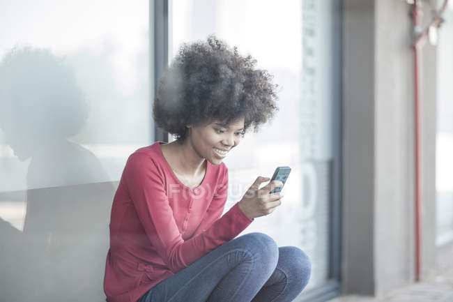 Giovane donna che legge messaggi su smart phone — Foto stock
