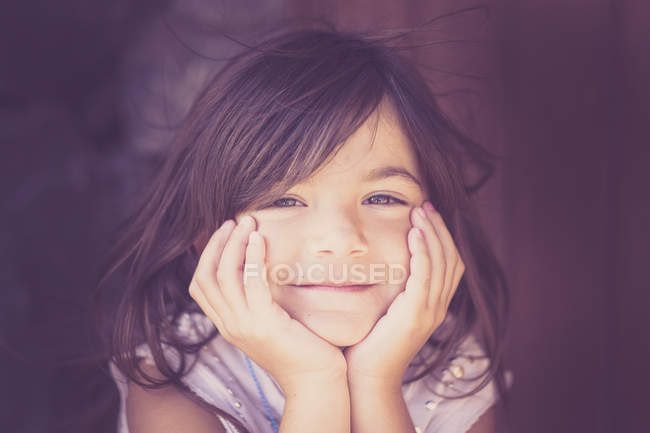 Portrait of smiling girl with head in her hands — Stock Photo