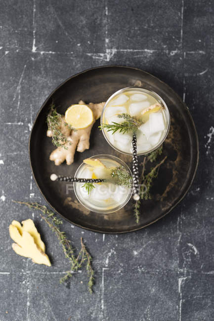 Top view of Lemon herb ginger lemonade, rosemary and thyme on wooden board — Stock Photo