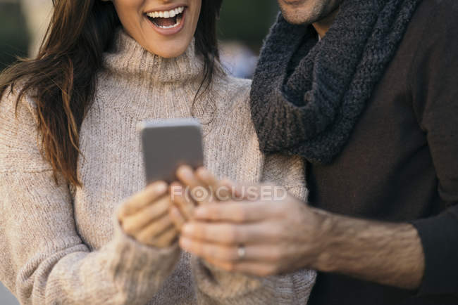 Close-up of happy Couple using cell phone — Stock Photo