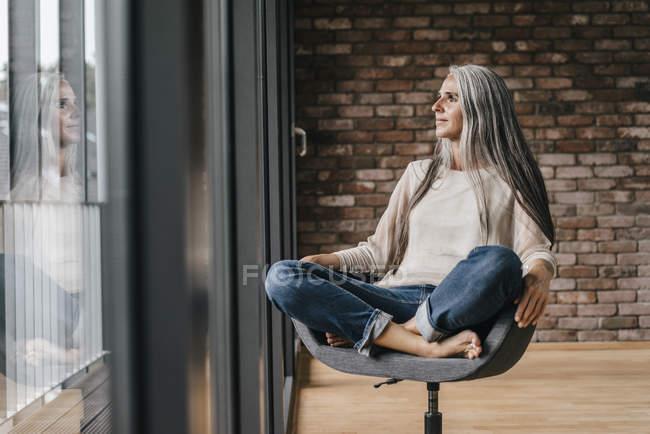 Femme avec des cheveux long gris assis sur une chaise à la fenêtre dans le Bureau — Photo de stock