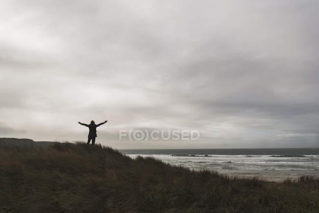 Homem de pé na costa sob céu nublado espalhando armas — Fotografia de Stock