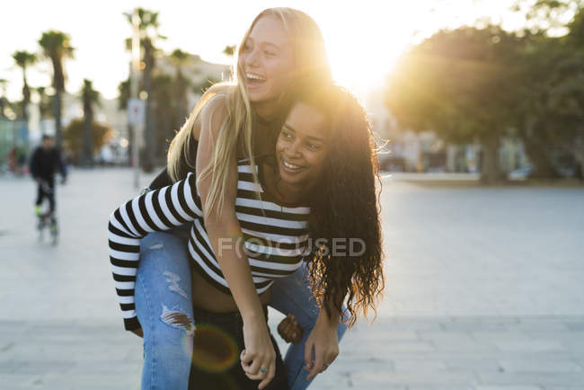 Two young women having fun on square at sunset — Stock Photo