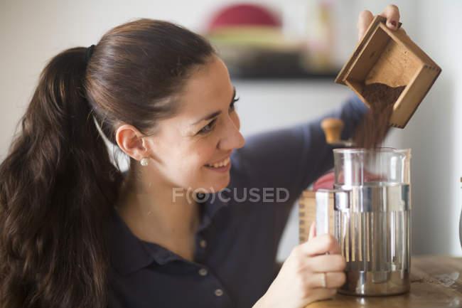 Усміхаючись жінка розливу кави порошок в скла кави — стокове фото