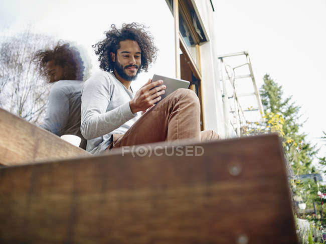 Young man looking at digital tablet on terrace — Stock Photo
