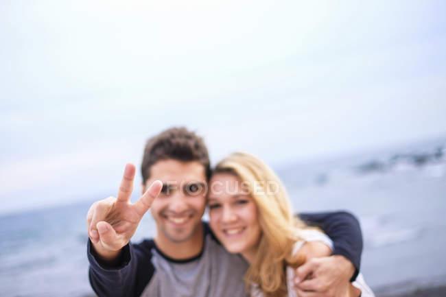 Щасливі молода пара embracing і робить знак перемоги — стокове фото