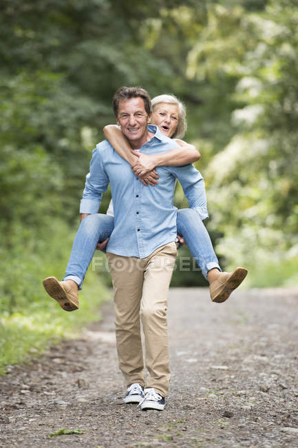 Active cute senior couple, man giving piggyback ride to woman in park — Stock Photo
