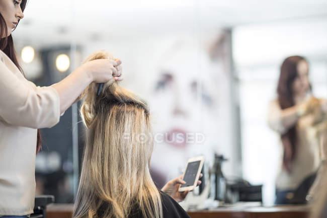 Parrucchiere in parrucchiere controllando i capelli del cliente — Foto stock