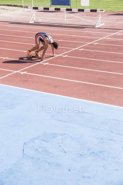 Бегун на тартановой трассе в стартовой позиции на стадионе — стоковое фото
