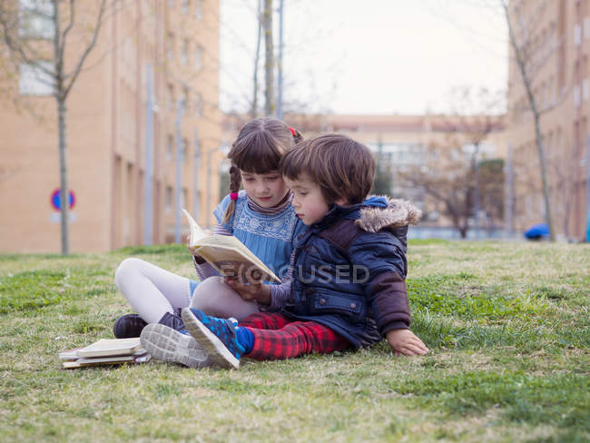 Little girl sitting with her brother on a lawn watching a book — Stock Photo