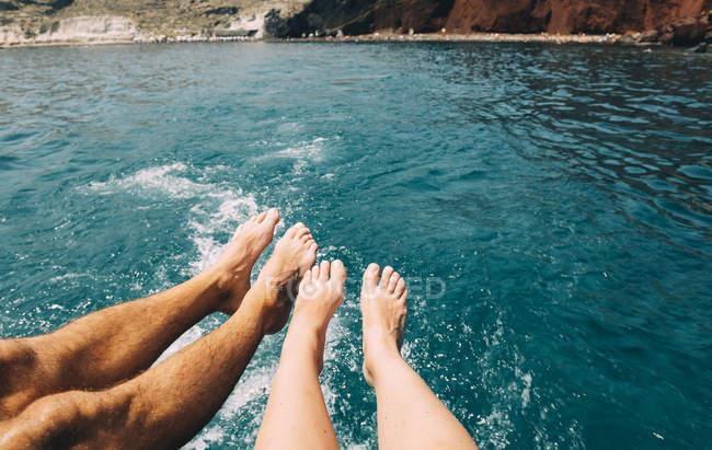 Grecia, Santorini, gambe di una coppia di fronte al mare — Foto stock