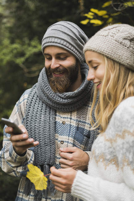 Young couple sharing cell phone outdoors in autumn — Stock Photo