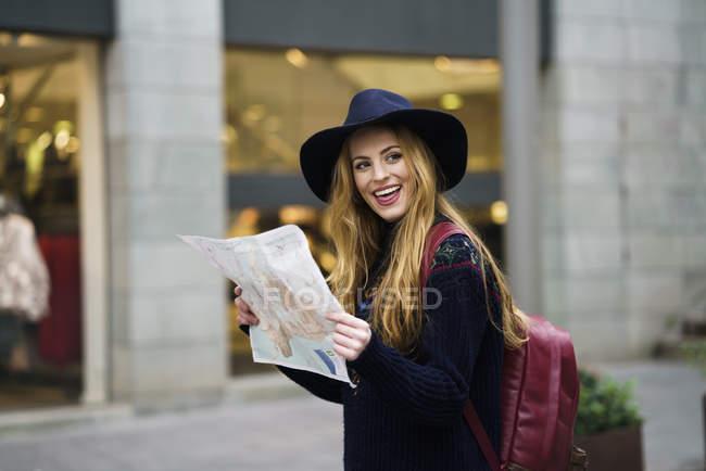 Ritratto di felice turistiche con mappa della città e lo zaino — Foto stock