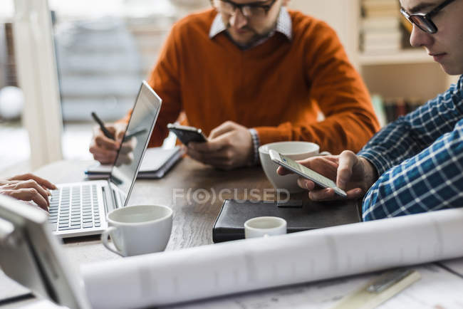 Colleagues at desk with smartphones, laptop and plan — Stock Photo