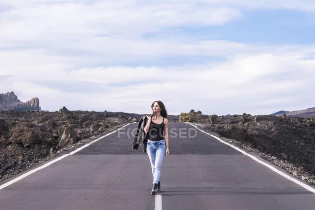 Spain, Tenerife, woman walking on an empty road — Stock Photo