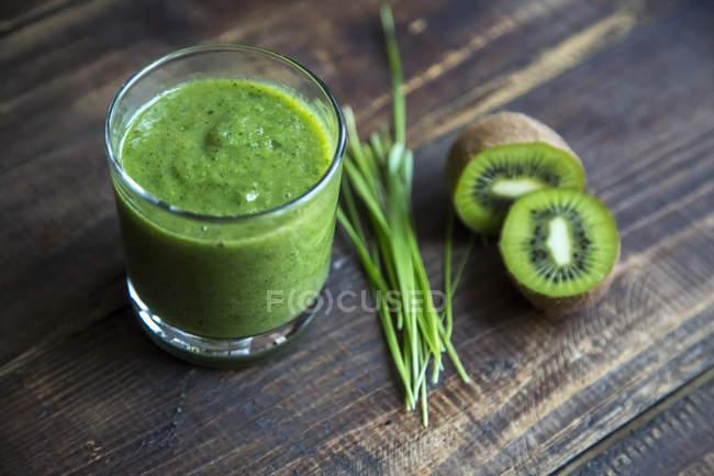 Smoothie de couve com kiwi e raygras orgânicos em madeira — Fotografia de Stock