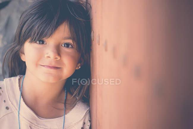 Retrato de menina sorridente encostada à parede — Fotografia de Stock