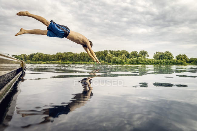 Man jumping from jetty into water — Stock Photo