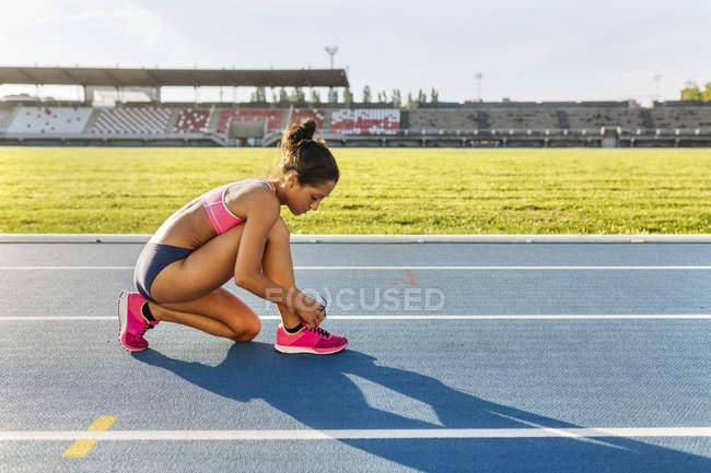 Боковой вид спортсменки, шьющей кроссовки на гоночной трассе — стоковое фото