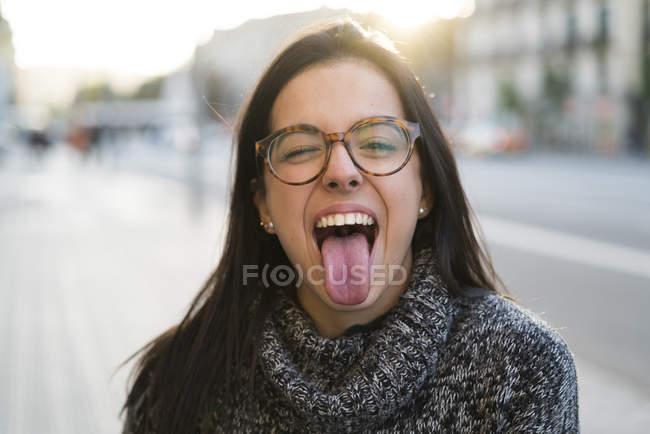 Ritratto di giovane donna felice con gli occhiali che sporgono la lingua — Foto stock