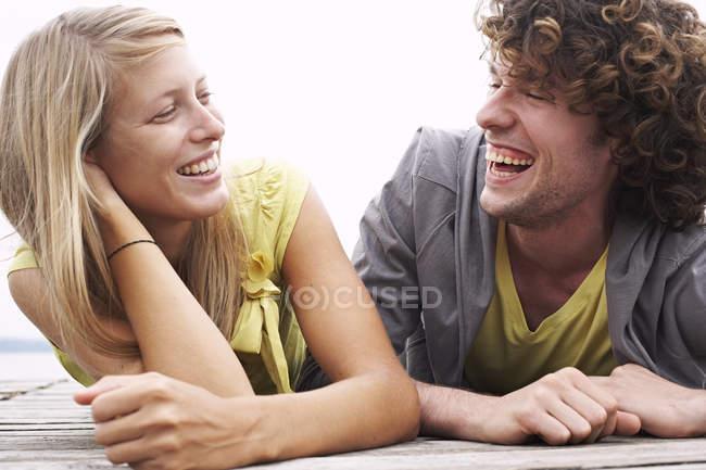 Сміючись молода пара, лежачи на на пристані — стокове фото