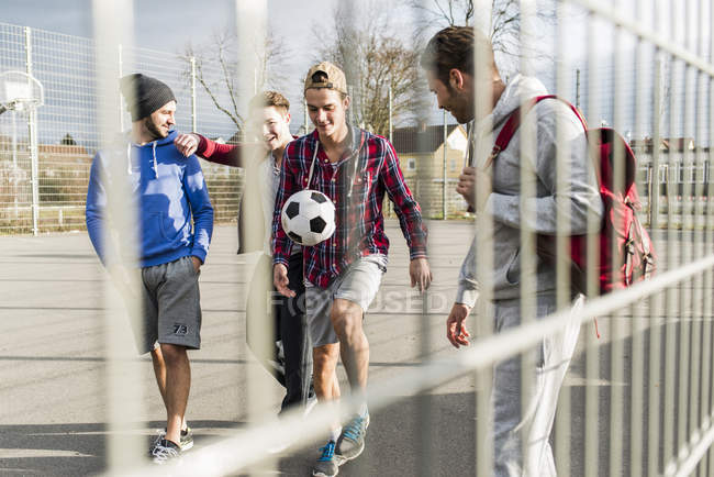 Vier junge Fußballer zu Fuß auf der Spielwiese mit Fußball — Stockfoto