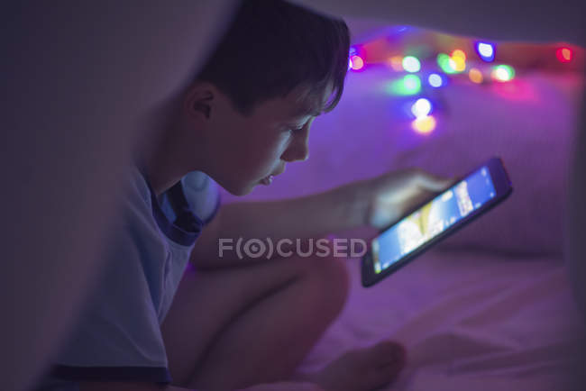 Boy sitting under a blanket looking at digital blanket — Stock Photo