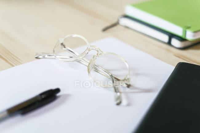 Окуляри на аркуші паперу на столі з ноутбуками і ручки — стокове фото
