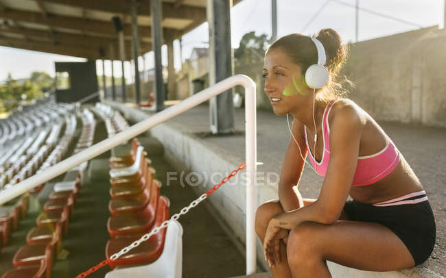 Sportswoman in headphones listening music in an athletics stadium — Stock Photo