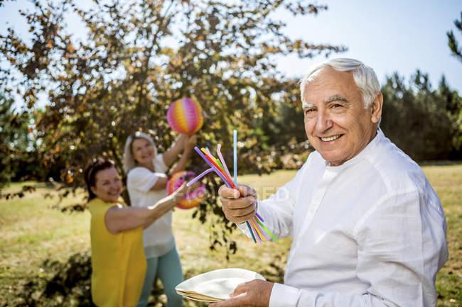 Портрет посміхаючись старший чоловік з соломкою і паперу пластин на луг з жінками на тлі — стокове фото