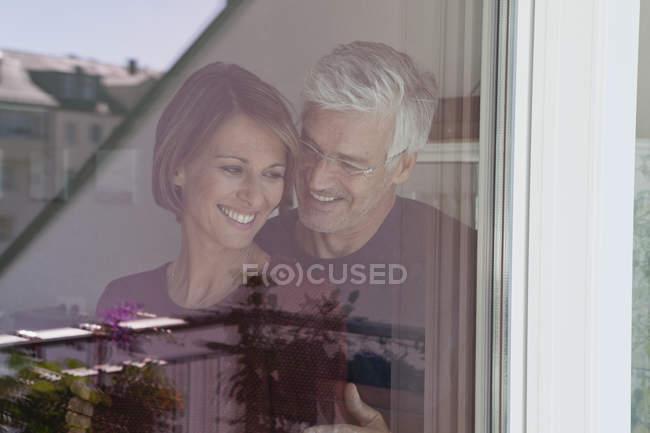 Pareja sonriente detrás de cristal de la ventana - foto de stock