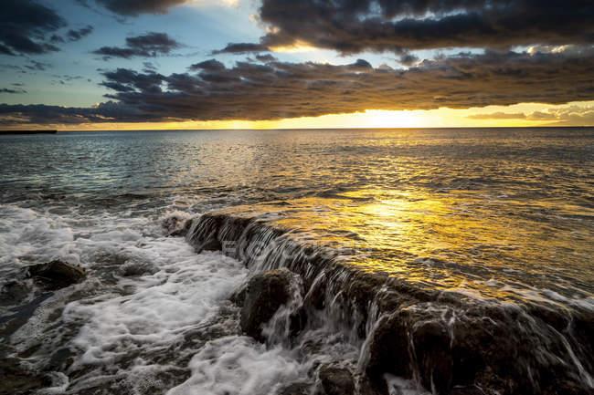 Espagne, Tenerife, vague dans la lumière du coucher du soleil avec des nuages sur le ciel — Photo de stock