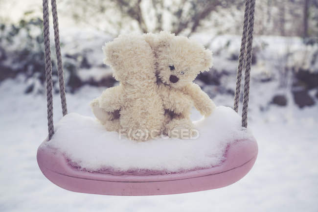 Two clasping teddy bears on snow-covered swing — Stock Photo