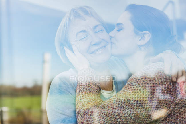 Молодая женщина целует пожилую женщину за стеклом — стоковое фото