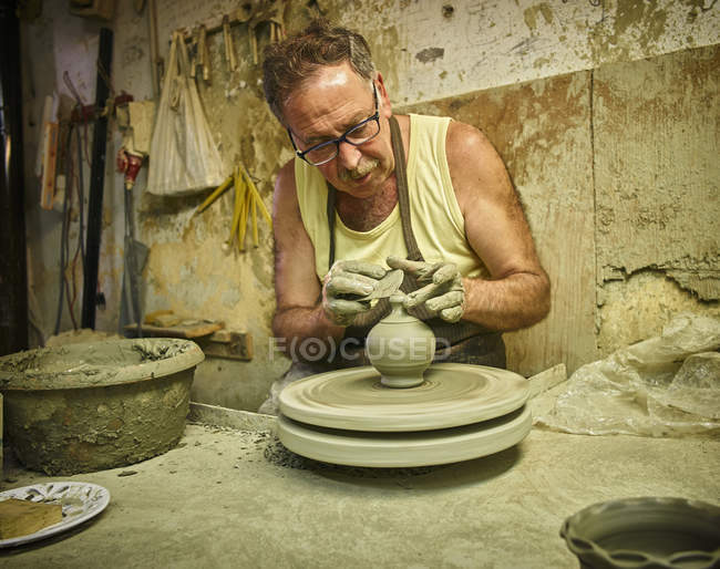 Potter in workshop working on earthenware vessel — Stock Photo