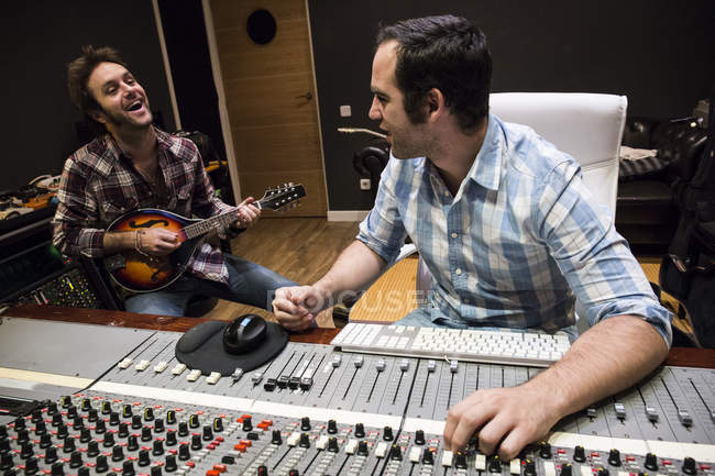 Guitar player and audio engineer in a recording studio — Stock Photo