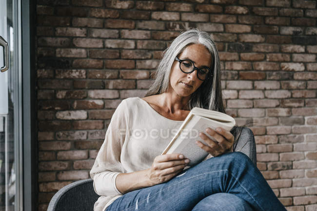 Woman with long grey hair sitting on chair and reading book — Stock Photo
