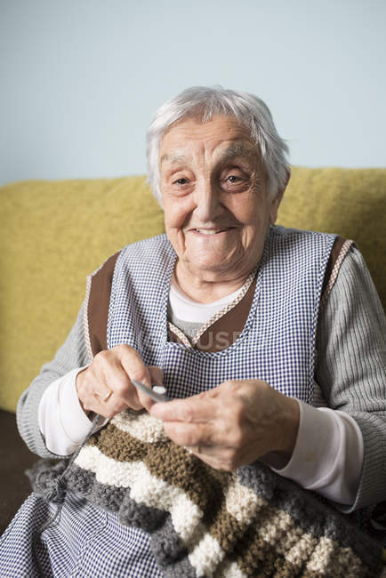 Portrait of smiling senior woman knitting — Stock Photo