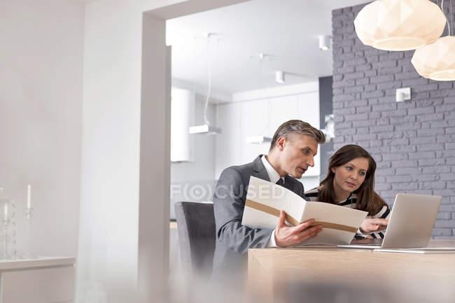 Businessman with portfolio and laptop talking to woman — Stock Photo